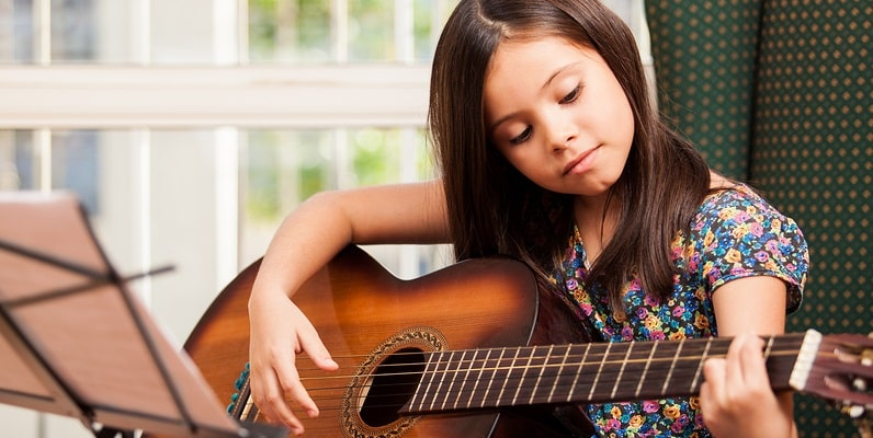 A girl learning guitar.